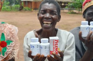 An African woman who is smiling while holding up boxes of medication.